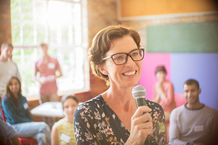 Audience behind smiling speaker with microphone at community centerの写真素材 [FYI02166680]
