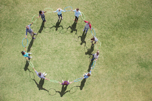 Team connected in circle by plastic hoops in sunny fieldの写真素材 [FYI02166684]