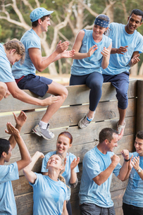 Team clapping and celebrating at wall on boot camp obstacle courseの写真素材 [FYI02166691]