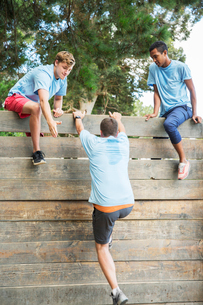 Teammates helping man over wall at boot camp obstacle courseの写真素材 [FYI02166696]