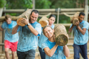 Determined people running with logs on boot camp obstacle courseの写真素材 [FYI02166700]