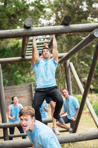 Determined man crossing monkey bars on boot camp obstacle courseの写真素材 [FYI02166721]
