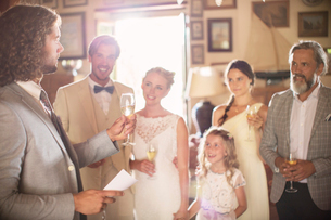 Best man toasting with champagne and giving speech during wedding reception in domestic roomの写真素材 [FYI02166726]