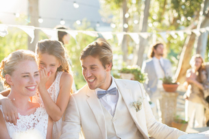 Bridesmaid whispering to bride's ear during wedding reception in domestic gardenの写真素材 [FYI02166732]