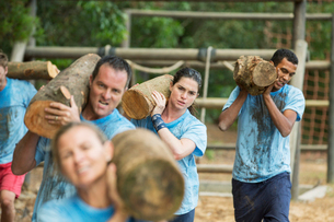 Determined team carrying logs on boot camp race courseの写真素材 [FYI02166747]