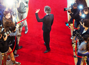 Celebrity arriving at red carpet event and waving at photographing paparazziの写真素材 [FYI02166756]