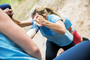 Teammates helping woman climb boot camp obstacle courseの写真素材 [FYI02166760]