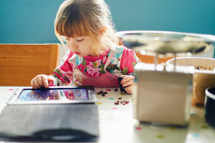 Curious girl using digital tabletの写真素材 [FYI02166769]
