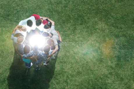 Team huddled in circle around glowing orb in fieldの写真素材 [FYI02166774]