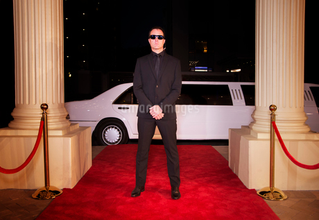 Serious bodyguard in sunglasses protecting red carpet at eventの写真素材 [FYI02166778]