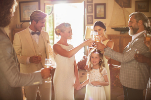 Young couple and guests toasting with champagne during wedding reception in domestic roomの写真素材 [FYI02166785]