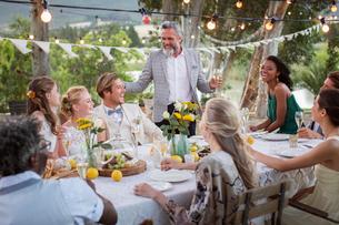 Best man speaking during wedding reception in domestic gardenの写真素材 [FYI02166799]
