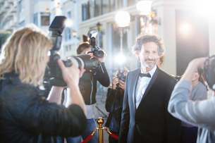 Smiling celebrity in tuxedo being photographed by paparazzi at red carpet eventの写真素材 [FYI02166800]