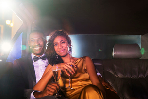 Smiling celebrity couple drinking champagne inside limousine outside eventの写真素材 [FYI02166802]