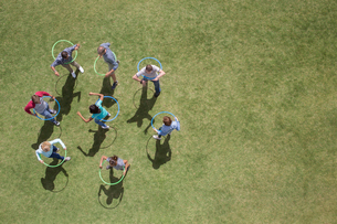 People spinning in plastic hoops in sunny grassの写真素材 [FYI02166806]