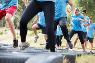 Determined people jumping tires on boot camp obstacle courseの写真素材 [FYI02166811]