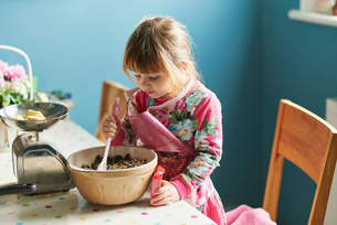 Curious girl baking with mixing bowl in kitchenの写真素材 [FYI02166828]