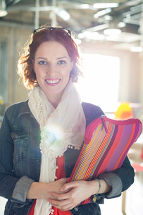 Portrait of smiling casual businesswoman holding laptop caseの写真素材 [FYI02166834]