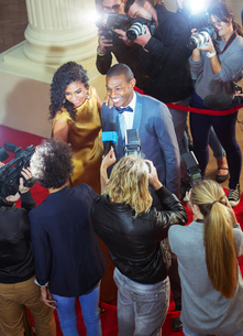 Celebrity couple being interviewed and photographed by paparazzi at red carpet eventの写真素材 [FYI02166849]