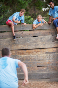 Teammates at wall cheering man on boot camp obstacle courseの写真素材 [FYI02166870]