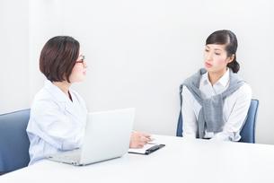 社内にてカウンセリングをする女性社員とカウンセラーの写真素材 [FYI02166896]