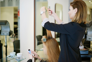 Hairdresser wrapping customer's hair in curlers in salonの写真素材 [FYI02166981]