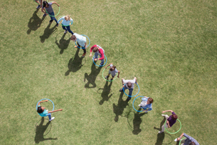 People spinning in plastic hoops in sunny fieldの写真素材 [FYI02166990]