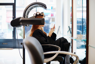 Woman sitting under dryer texting with cell phone in hair salonの写真素材 [FYI02166994]
