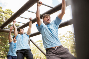 Determined men crossing monkey bars on boot camp obstacle courseの写真素材 [FYI02166998]