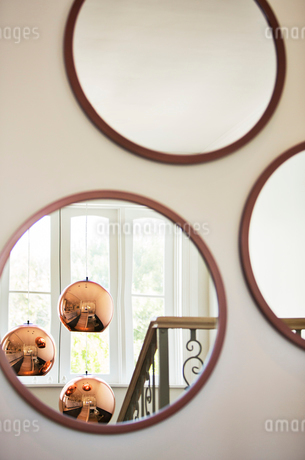 Reflection of copper pendant lights in round mirrorの写真素材 [FYI02167008]