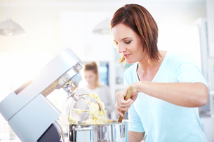 Woman baking with stand mixer in kitchenの写真素材 [FYI02167043]