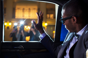 Celebrity in limousine waving at paparazzi photographersの写真素材 [FYI02167067]