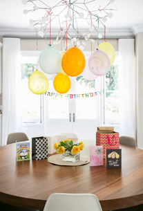 Smiley face balloons and Happy Birthday sign hanging over table with cardsの写真素材 [FYI02167086]