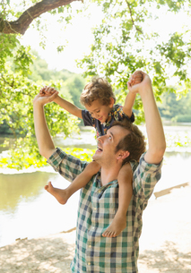 Playful father carrying son on shoulders at lakesideの写真素材 [FYI02167108]