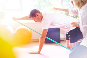 Physical therapist guiding man pulling resistance bandの写真素材 [FYI02167152]