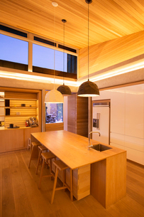 Illuminated slanted wood ceiling and pendant lights over kitchen islandの写真素材 [FYI02167160]