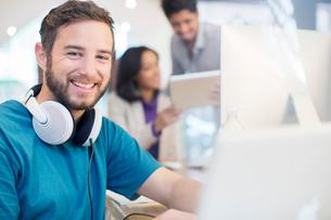 Portrait confident creative businessman with headphones working in officeの写真素材 [FYI02167200]