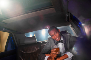 Portrait of confident celebrity drinking cocktail inside limousine outside eventの写真素材 [FYI02167214]