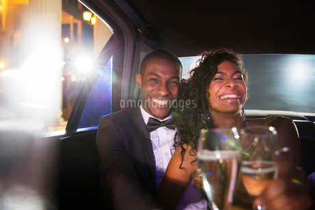 Laughing celebrity couple drinking champagne inside limousine at red carpet eventの写真素材 [FYI02167253]