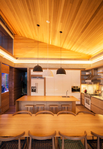 Illuminated slanted wood ceiling over luxury kitchen and dining tableの写真素材 [FYI02167260]