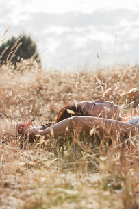 Serene woman sleeping in sunny rural fieldの写真素材 [FYI02167269]
