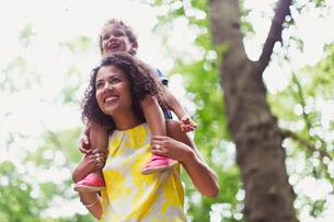 Smiling mother carrying son on shoulders below treeの写真素材 [FYI02167286]