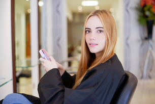 Portrait woman texting with cell phone in hair salonの写真素材 [FYI02167304]