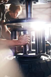 Mechanic using tire machinery in auto repair shopの写真素材 [FYI02167308]