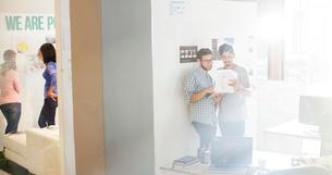 Creative businessmen reviewing paperwork in sunny officeの写真素材 [FYI02167310]