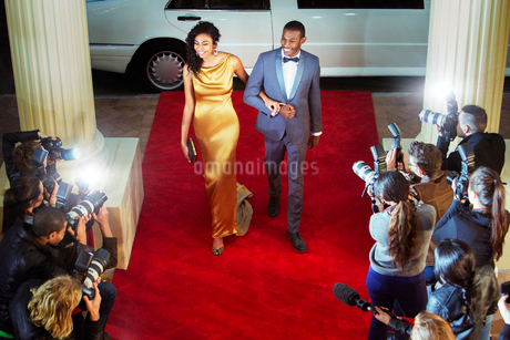 Celebrity couple arriving at red carpet event and being photographed by paparazziの写真素材 [FYI02167331]