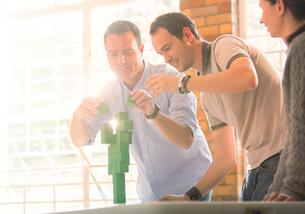 Businessmen balancing green blocksの写真素材 [FYI02167346]