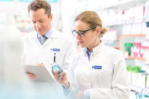 Pharmacist reading label on bottle in pharmacyの写真素材 [FYI02167388]