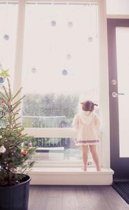 Curious girl on window ledge below Christmas ornamentsの写真素材 [FYI02167402]