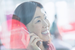 Close up smiling businesswoman talking on cell phoneの写真素材 [FYI02167411]